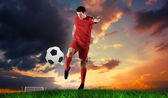 Football player in red kicking — Stock Photo