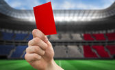 Hand holding up red card — Stockfoto