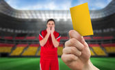 Hand holding up yellow card — Stock Photo