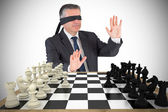 Mature businessman in blindfold with chessboard — Stock Photo