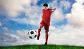 Football player in red kicking — Stockfoto