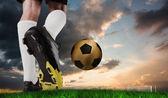 Football boot kicking gold ball — Stock Photo