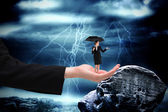 Businesswoman holding umbrella in large hand — Stock Photo