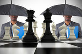 Composite image of businessman standing under umbrella with ches — Stock Photo