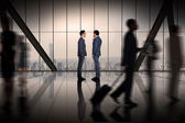 Businessmen talking against room — Stock Photo