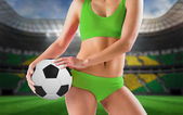 Girl in bikini holding football — Stock Photo