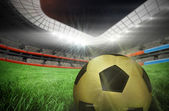 Gold football against football pitch — Stockfoto