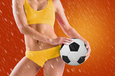 Girl in yellow bikini holding football — Stockfoto
