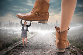 Cowboy boots stepping on businesswoman — Stock Photo