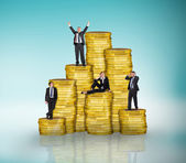 Business people on pile of coins — Stockfoto