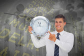 Businessman holding and showing clock — Stockfoto