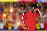 Disappointed football fan looking down — Stockfoto
