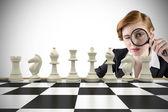 Businesswoman with magnifying glass with chessboard — Stock Photo