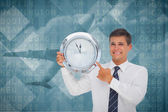Businessman holding and showing clock — Stok fotoğraf