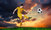 Football player in yellow kicking — Stock Photo