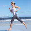 Blonde jogging on the beach barefoot — Stock Photo #48323923