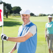 Golfer holding eighteenth hole flag with partner — Stock Photo #48325657