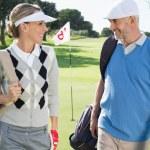 Golfing couple walking away from eighteenth hole — Stock Photo