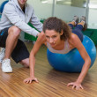 Trainer helping his client doing push up — Stock Photo #48327709