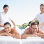 Couple enjoying couples massage poolside — Stock Photo