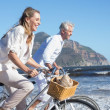 Couple riding their bikes on the beach — Stock Photo #48328143