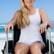Постер, плакат: Wheelchair bound blonde on beach