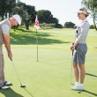 Golfing couple on putting green at eighteenth hole — Stock Photo #48328531