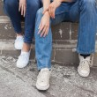 Hip couple in denim sitting on steps — Stock Photo #48328557