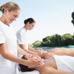 Couple enjoying head massages poolside — Stock Photo #48329721