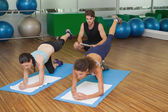 Women in pilates position with trainer — Stok fotoğraf