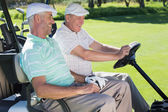 Golfing friends laughing in golf buggy — Stock Photo