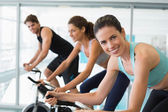 Fit people in a spin class with brunette — Stock Photo