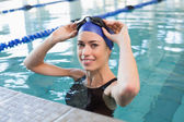 Fit swimmer in the pool smiling — Stock Photo