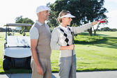 Golfing couple looking at course with golf buggy — Stock Photo