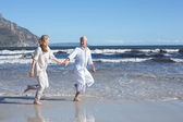 Couple skipping barefoot on the beach — Stock Photo