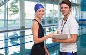 Swimmer with her coach by the pool — Stock Photo