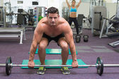 Shirtless bodybuilder about to lift heavy barbell — Foto Stock