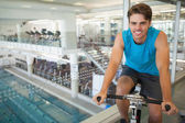 Smiling fit man on the spin bike — Stock Photo