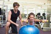 Trainer and client balance on exercise ball — Stockfoto