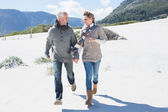 Couple skipping on the beach in warm clothing — Stock Photo