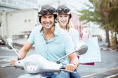 Couple riding scooter with shopping bags — Stock Photo