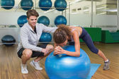 Trainer watching his client using exercise ball — ストック写真