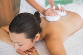 Brunette getting a herbal compress massage — Stockfoto