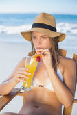 Blonde relaxing in deck chair with cocktail — Stock Photo