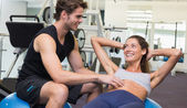 Trainer and client do sit ups on exercise ball — Stock Photo