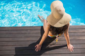 Brunette in bikini sitting by the pool — Stock Photo