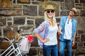 Hip couple standing by wall with bikes — Stock fotografie