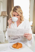 Blonde drinking coffee, reading newspaper — Stock Photo