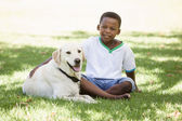 Boy sitting with labrador dog — Stok fotoğraf