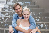 Couple sitting on steps smiling — Stock Photo